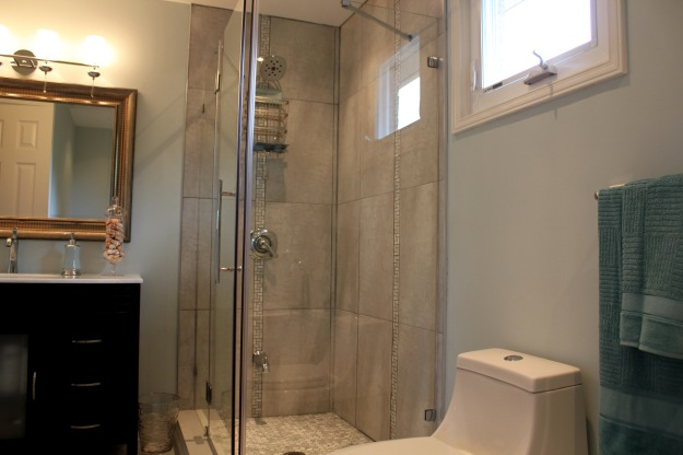 Picture showing new corner shower, toilet, vanity