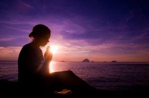 Woman sitting on beach, praying